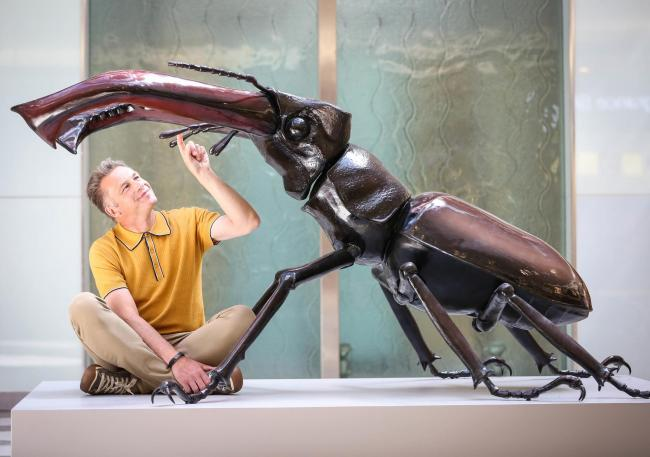 Chris Packham with a giant model of a stag beetle. Photo: Matt Alexander/PA.